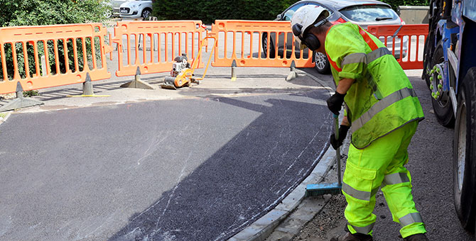 workman checking road surface quality