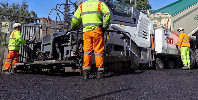 asphalt being laid by machine with DJT staff