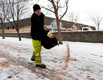 DJT staff gritting road with salt